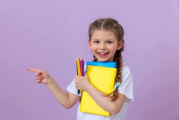 Mała dziewczynka z warkoczykami i książkami do czytania i nauki wskazuje na bok.
