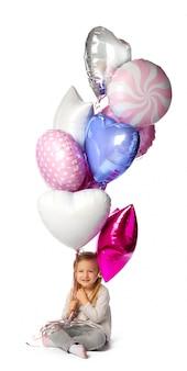 Mała dziewczynka z wiązką balonów siedzieć odizolowywam na białym tle