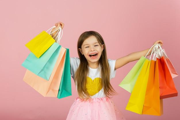 Mała dziewczynka z wieloma torba na zakupy na pastelowej menchii ścianie. dość radosna młoda dziewczyna w tiulowej spódnicy, z długimi blond włosami chodząca w kolorowych opakowaniach