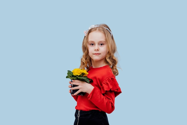Mała dziewczynka z wiosennym kwiatem w dłoni, ubrana na czerwono, odizolowana na niebiesko