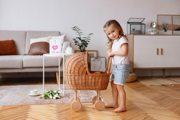 Mała dziewczynka z wózkiem zabawki w salonie