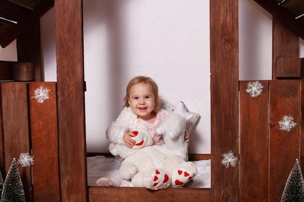 Mała dziewczynka z zabawkami w drewnianym domu. ozdoby świąteczne.