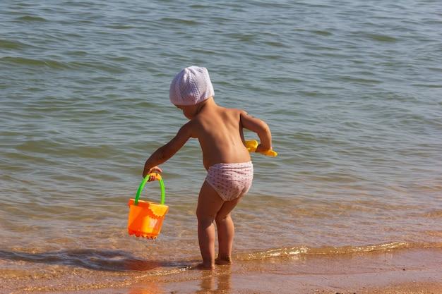 Mała dziewczynka z zabawkowym wiaderkiem i łopatą bawi się na piaszczystej plaży w letni dzień