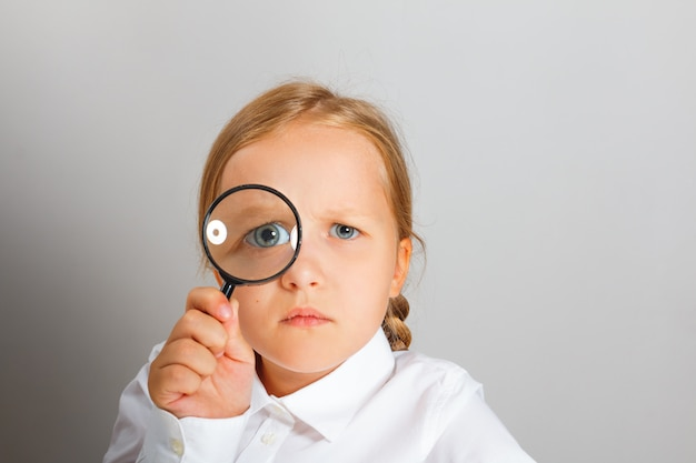 Mała dziewczynka z zainteresowaniem patrzy przez szkło powiększające.