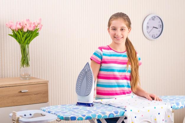 Mała dziewczynka z żelazkiem w pobliżu deski do prasowania