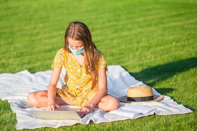 Mała dziewczynka za pomocą laptopa do nauki na świeżym powietrzu w parku