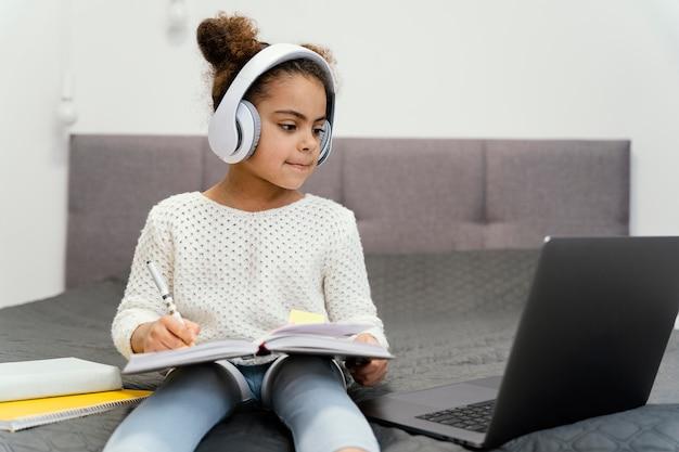 Mała dziewczynka za pomocą laptopa i słuchawek do szkoły online