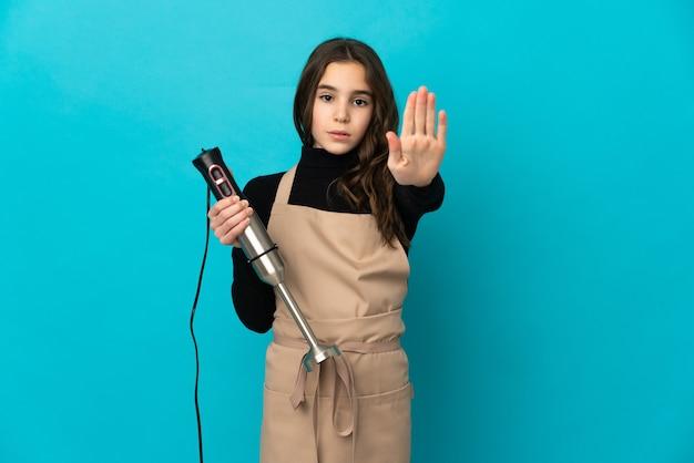 Mała dziewczynka za pomocą ręcznego miksera na białym tle na niebieskim tle co gest zatrzymania