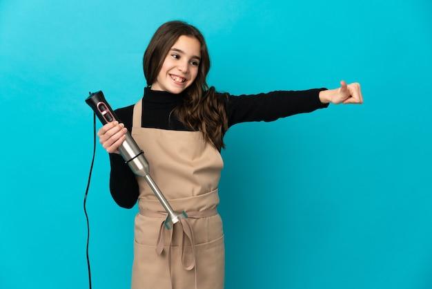 Mała dziewczynka za pomocą ręcznego miksera na białym tle na niebieskim tle, dając gest kciuki do góry