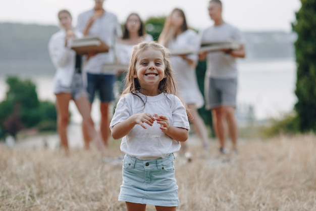 Mała dziewczynka zabawy na piknik, pizza, napoje, lato i trawnik