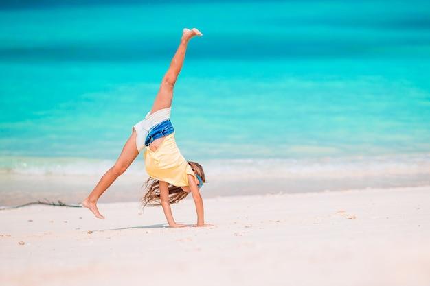 Mała dziewczynka zabawy na tropikalnej plaży podczas letnich wakacji na płytkiej wodzie.