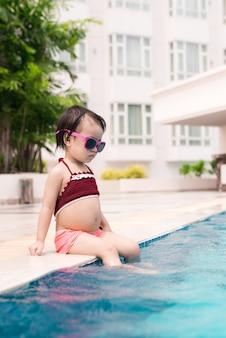 Mała dziewczynka zabawy w basenie. wakacje letnie i koncepcja wakacji
