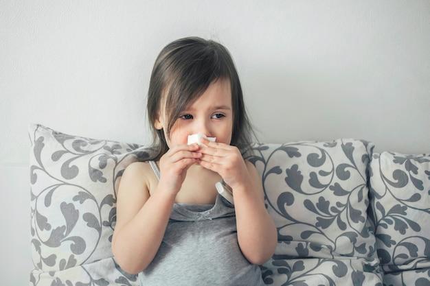 Mała dziewczynka zachorowała. dziecko ma gorączkę. dziecko jest smutne z powodu przeziębienia.