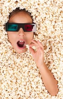 Mała dziewczynka zakopana w popcorn w okularach 3d
