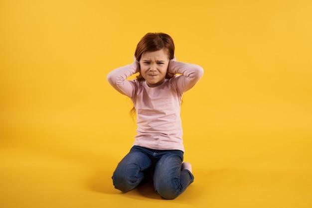 Mała dziewczynka zakrywa uszy. niezwykle głośno.
