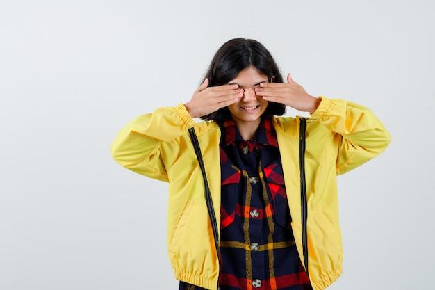 Mała dziewczynka zakrywająca oczy rękami w kraciastej koszuli, kurtce i patrząc wesoło