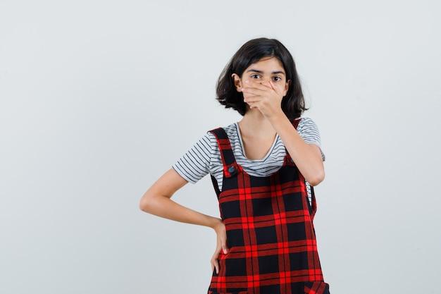 Mała dziewczynka zakrywająca usta ręką w t-shircie, kombinezonie i wyglądająca na zmartwioną,
