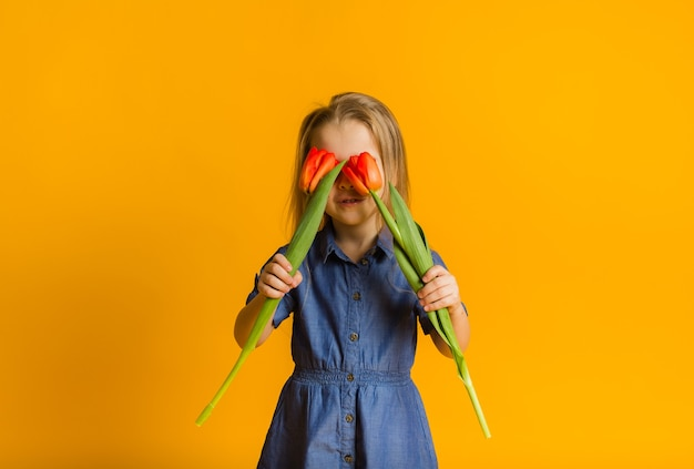 Mała dziewczynka zamknęła oczy czerwonymi tulipanami na żółtej ścianie