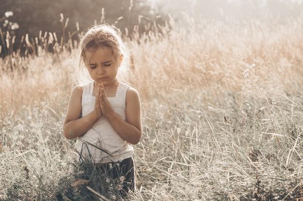 Mała dziewczynka zamknęła oczy, modląc się na świeżym powietrzu, ręce złożone w modlitwie o wiarę, duchowość i religię. pokój, nadzieja, koncepcja marzeń.