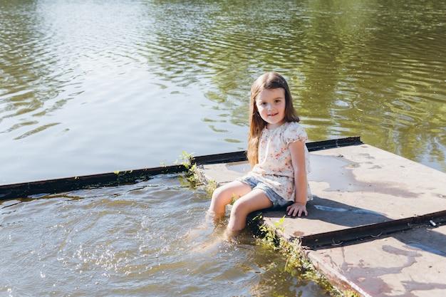 Mała dziewczynka zanurzanie stóp w wodzie i śmiejąc się