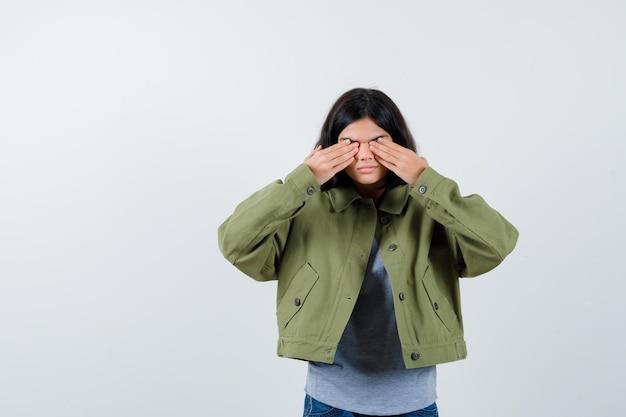 Mała dziewczynka zasłaniając oczy rękami w płaszczu, koszulce, dżinsach i patrząc poważnie, widok z przodu.
