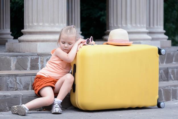 Mała dziewczynka zasnęła na dużej żółtej walizce. słodkie dziecko jest zmęczone podróżowaniem.