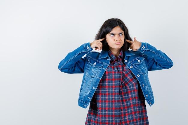 Mała dziewczynka zatykając uszy palcami w koszulę, kurtkę i patrząc zamyślony, widok z przodu.
