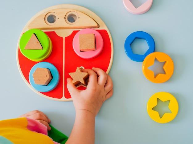 Mała dziewczynka zbiera drewniane kolorowe sortownik bezpieczne naturalne drewniane zabawki dla dzieci