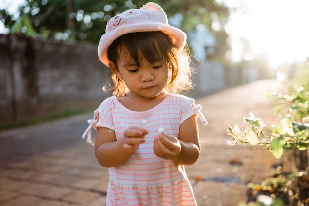 Mała dziewczynka zbiera kolorowe kwiaty w parku