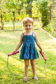 Mała dziewczynka ze skakanką stojąca w ogrodzie w słoneczny dzień