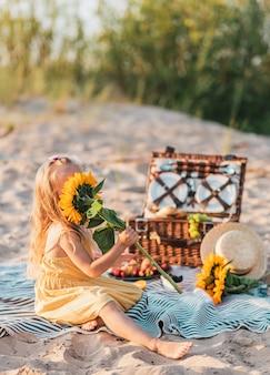 Mała dziewczynka ze słonecznikiem, letni piknik na plaży