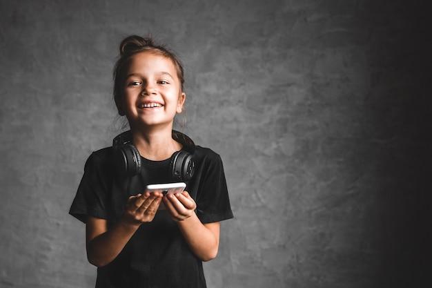 Mała dziewczynka ze słuchawkami i telefonem na szarej ścianie