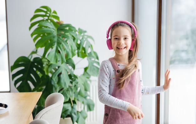 Mała dziewczynka ze słuchawkami stoi w pomieszczeniu w domu, patrząc na kamery.