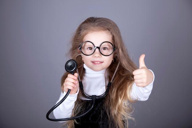 Mała dziewczynka ze stetoskopem pokazuje ok.