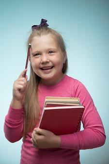 Mała dziewczynka ze stosem książek i ołówkiem w dłoniach na niebieskiej ścianie. powrót do koncepcji szkoły i edukacji