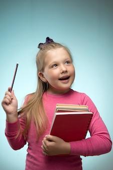 Mała dziewczynka ze stosem książek i ołówkiem w dłoniach. powrót do koncepcji szkoły i edukacji