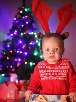 Mała dziewczynka ze świątecznymi rogami jelenia siedzi w pudełku prezentowym