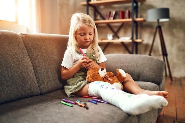 Mała dziewczynka ze złamaną nogą na kanapie. dziecko rysuje flamastrami na bandażu gipsowym.
