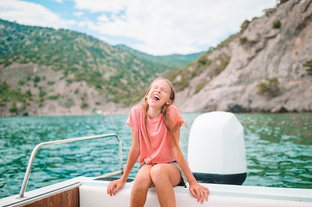 Mała dziewczynka żeglowanie łodzią w czyste morze