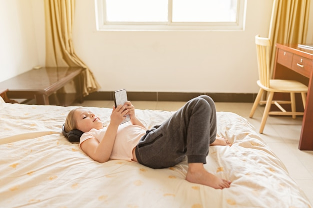 Mała dziewczynka zostaje w domu i używa telefon komórkowego z blondynka włosy