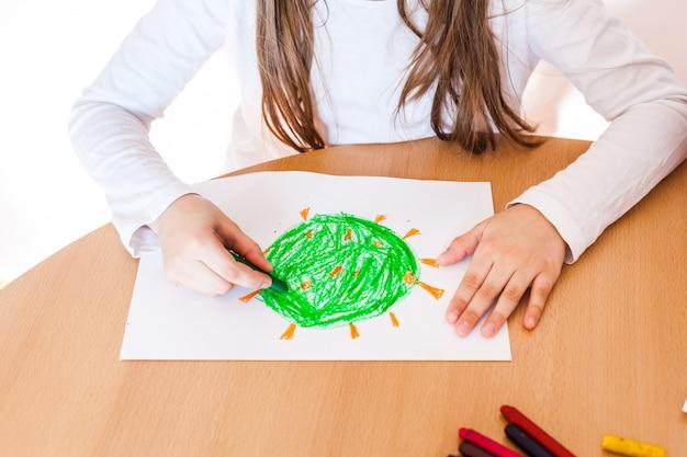 Mała dziewczynka zrobiła rysunek bakterii koronawirusa. rysunki kredkami na papierze. mała dziewczynka martwiła się o covid-19