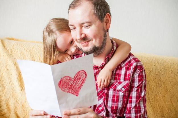 Mała dziewczynka życzy tacie szczęśliwego dnia ojca. córka przytula tatę, daje kartę z rysunkiem serca