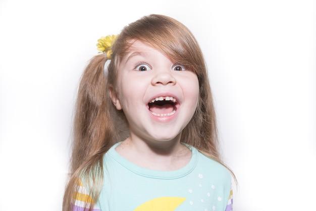 Mała emocjonalna dziewczyna raduje się ze zdziwienia na białym tle