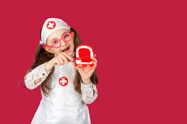 Mała fajna dziewczyna dentysta lekarz w kombinezonie medycznym