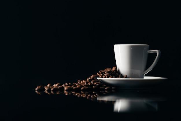 Mała filiżanka czarnej kawy na ciemnym tle z ziaren kawy