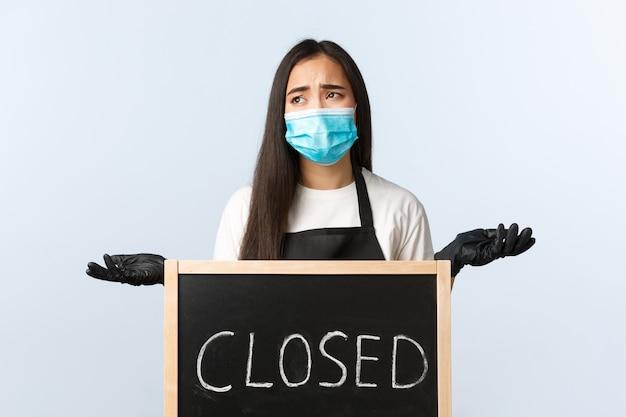 Mała firma, pandemia covid-19, zapobieganie koncepcji wirusów i pracowników. niespokojny i zdenerwowany pracownik lub właściciel kawiarni skarży się na blokadę koronawirusa, nie może pracować, wzrusza ramionami w pobliżu zamkniętego znaku