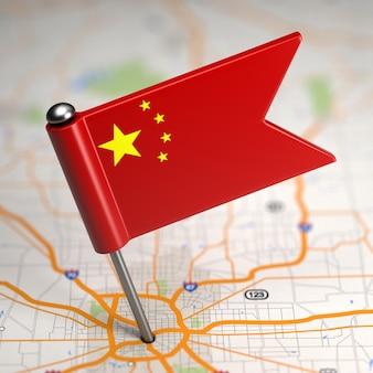 Mała flaga chińskiej republiki ludowej na tle mapy z selektywną ostrością.