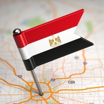 Mała flaga egiptu naklejona na tle mapy z selektywną ostrością.