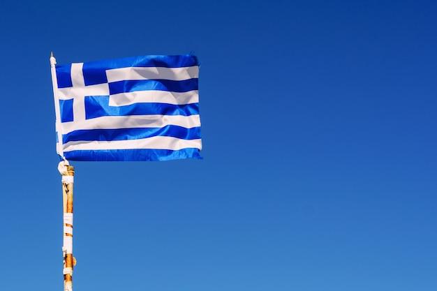 Mała flaga grecji macha na wietrze na tle błękitnego nieba