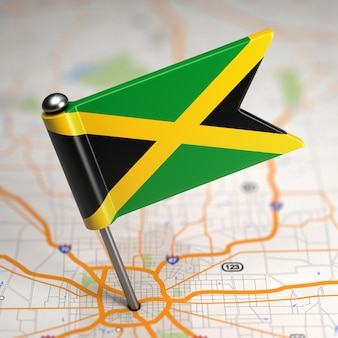 Mała flaga jamajki na tle mapy z selektywną ostrością.